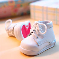 White lace up baby booties with red undersole.