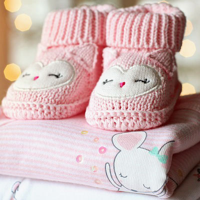 Pink baby booties and baby clothes. New baby messages for greeting cards.