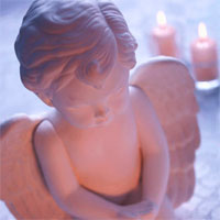 Sweet ceramic baby angel with candles.